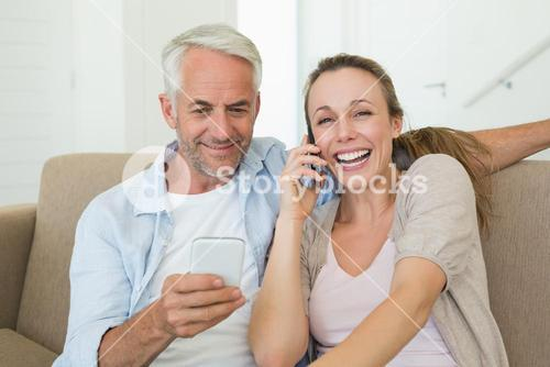Happy couple sitting on couch talking and texting on their phones