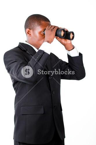 Young businessman looking with binoculars downwards