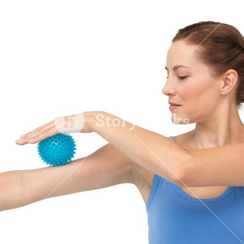 Portrait of a young woman holding stress ball on arm