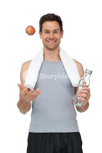 Smiling fit young man with apple and water bottle
