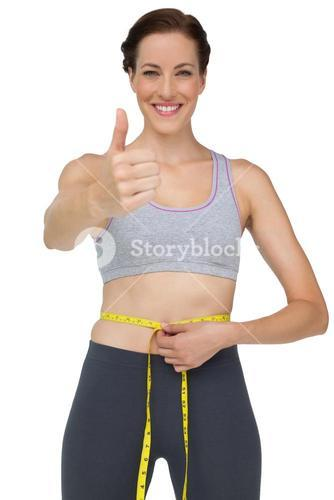 Fit woman measuring waist while gesturing thumbs up