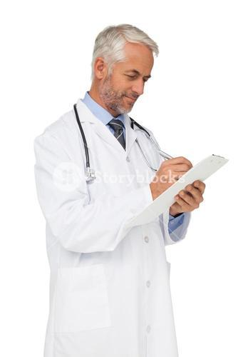 Concentrated male doctor writing reports
