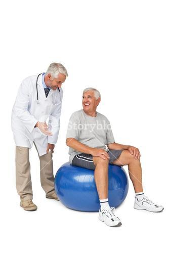 Male therapist looking at senior man sit on exercise ball