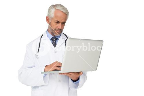Concentrated male doctor using laptop