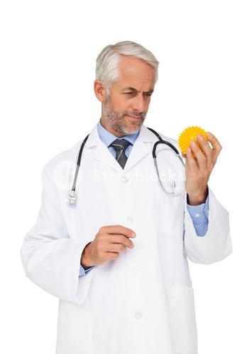 Concentrated male doctor looking at stress ball