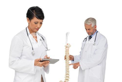 Doctor holding digital table with colleague by skeleton model