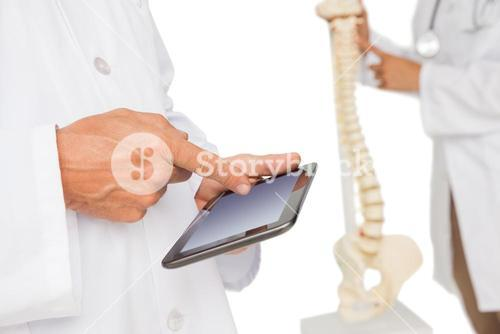 Mid section of doctors with digital table and skeleton model