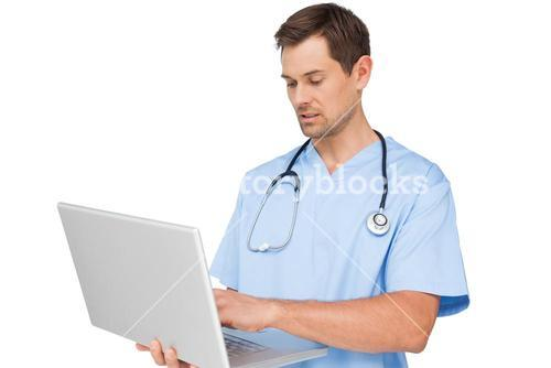Concentrated male surgeon using laptop