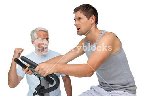 Determined young man on stationary bike with trainer