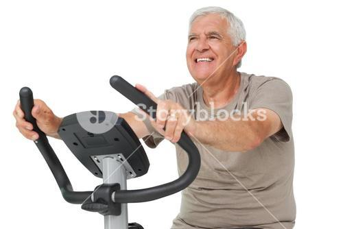 Portrait of a happy senior man on stationary bike