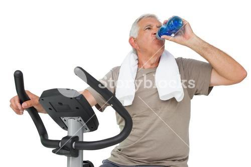 Senior man drinking water on stationary bike