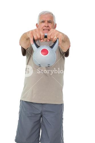 Portrait of a senior man exercising with kettle bell