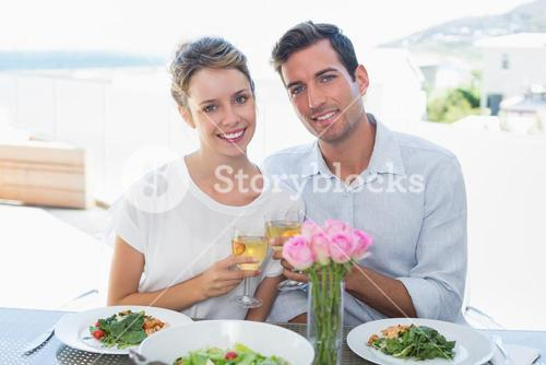 Couple toasting wine glasses at lunch table