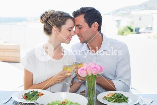 Loving couple toasting wine glasses at lunch table