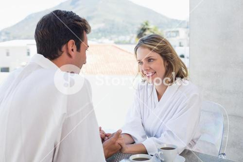 Loving couple holding hands at home
