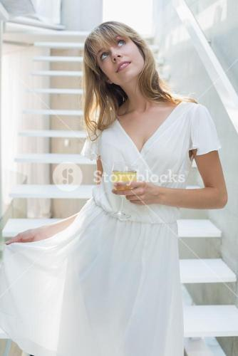 Thoughtful beautiful woman with wine glass on stairs