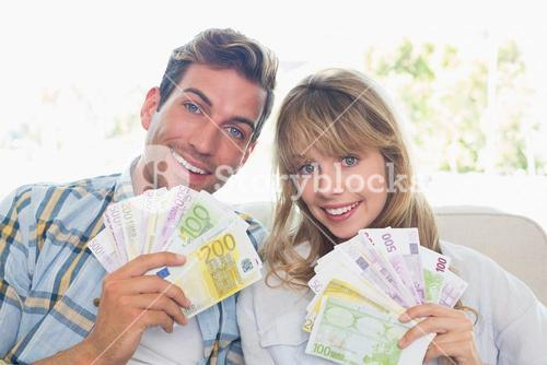 Portrait of a young couple holding fanned out Euro notes
