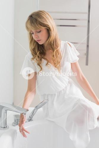 Beautiful young woman sitting on the edge of bath tub