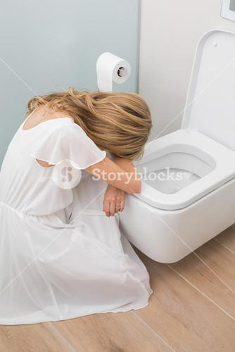 Sick young woman sitting in the toilet
