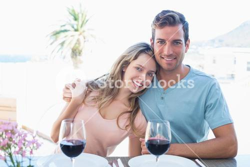 Loving couple with wine glasses at dining table