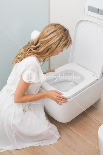 Woman about to vomit into a toilet