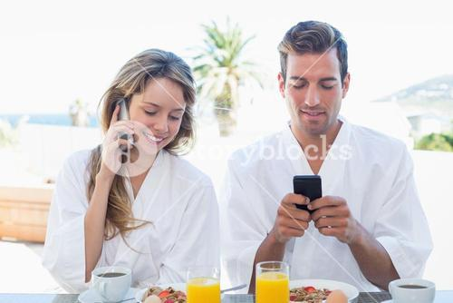 Couple using mobile phones while having breakfast