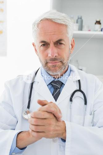Serious confident male doctor at medical office