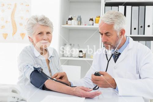 Doctor taking blood pressure of his retired patient
