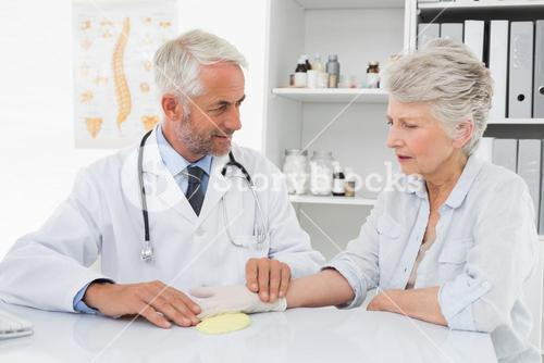 Doctor taking a senior females pulse