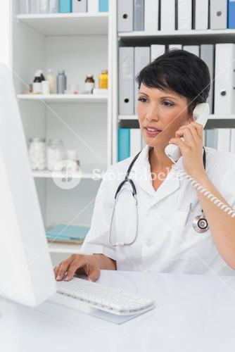 Concentrated doctor using computer and telephone