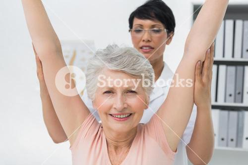 Female physiotherapist with senior woman raising hands