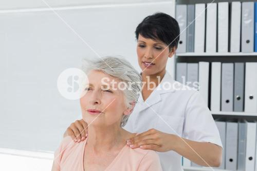 Chiropractor massaging a senior womans shoulder