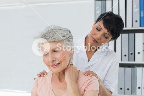 Chiropractor looking at senior woman with neck pain
