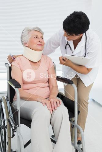 Doctor talking to senior patient in wheelchair with cervical collar