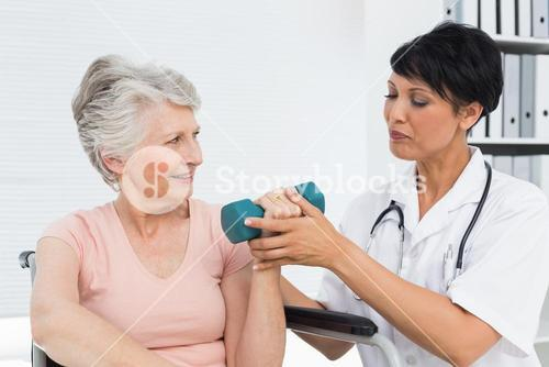 Physiotherapist assisting senior woman to lift dumbbell