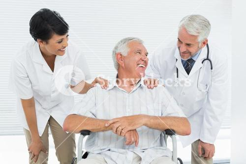 Happy senior patient with doctors sitting in wheelchair
