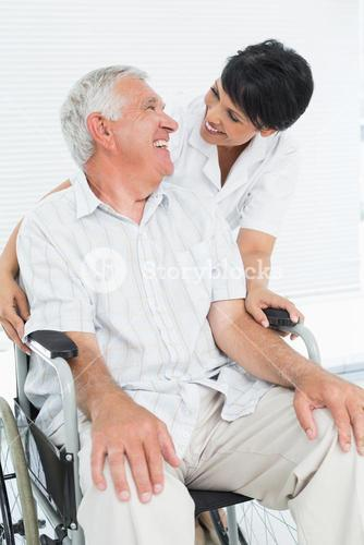Portrait of a nurse with senior patient sitting in wheelchair
