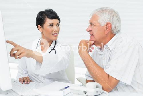Doctor with male patient reading reports on computer