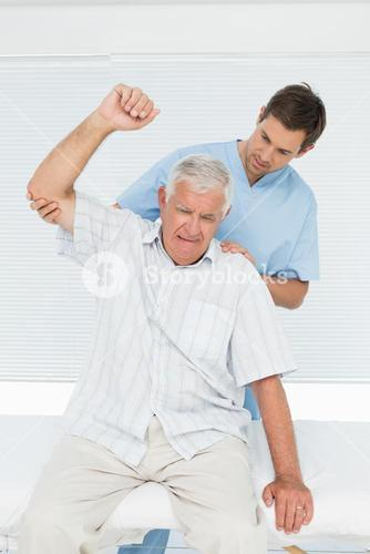 Mhysiotherapist assisting senior man to raise hand