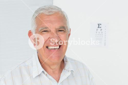 Smiling senior man with eye chart in the background