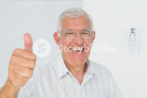 Smiling senior man gesturing thumbs up with eye chart in background