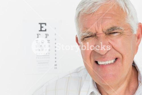Portrait of a senior man with eye chart in background