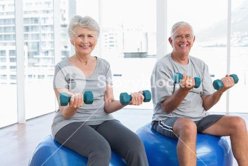Happy senior couple sitting on fitness balls with dumbbells