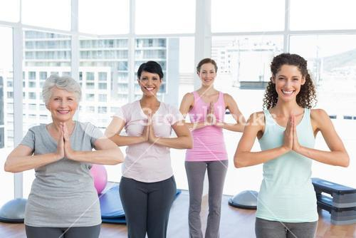 Class standing in namaste pose at yoga class