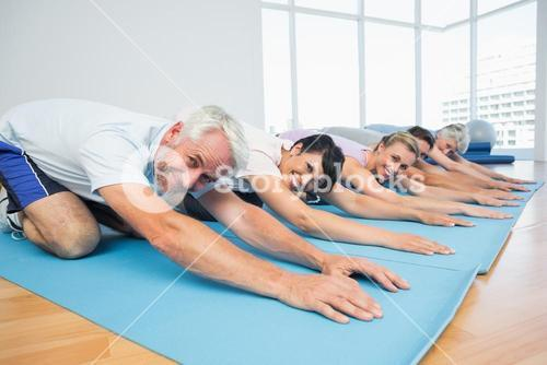 Portrait of fitness group bowing in row