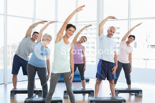 Class stretching hands in yoga class