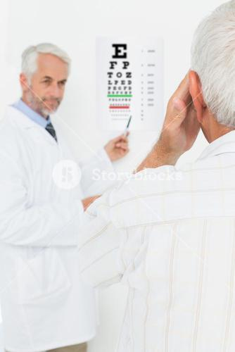 Pediatrician ophthalmologist with senior patient pointing at eye chart