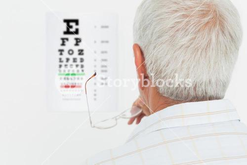 Rear view of a senior man looking at eye chart