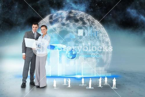 Happy business team using laptop with interface and human representations