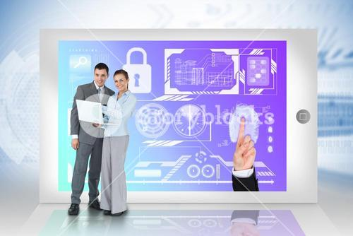 Happy business team using laptop with security interface on tablet
